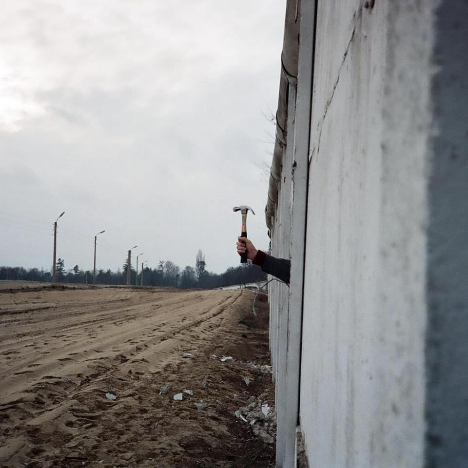 Michael Dunn, a young American soldier stationed in West Berlin, pokes his hand through the open Berlin Wall in 1989.